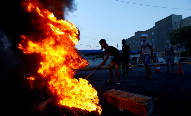 Iraqi demonstrators burn tires to block the road during a protest over poor public services in the holy city of Najaf. Credit: Reuters Photo