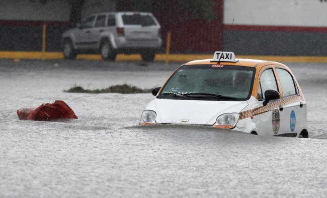 A taxi driver is seen crossing a flooded street during the Storm Hanna in Apodaca on the outskirts of Monterrey, Mexico. Credit: Reuters Photo