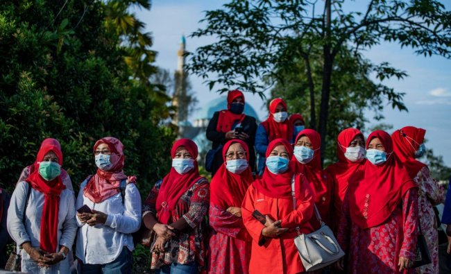 Supporters of Malaysia\'s former prime minister Najib Razak wear face masks while standing outside the gate of the Duta Court complex awaiting a verdict in his corruption trial in Kuala Lumpur on July 28, 2020. Credit: AFP Photo