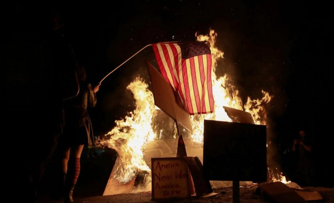 A demonstrator sets fire to an American flag during a protest against racial inequality and police violence in Portland, Oregon, US. Credit: Reuters Photo