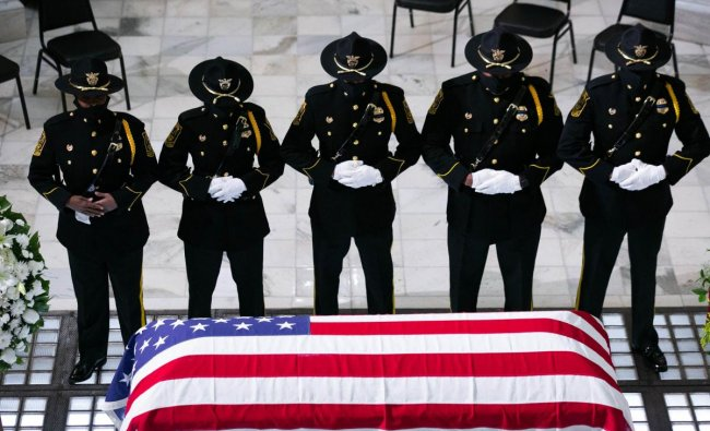 Members of the Fulton County Sheriff\'s Office Honor Guard stand at attention in front of former US Rep. John Lewis (D-GA) as he lies in state at the Georgia State Capitol. Credit: AFP Photo