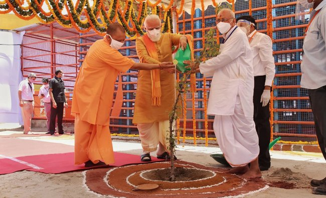Prime Minister Narendra Modi along with Uttar Pradesh Chief Minister Yogi Adityanath waters Parijaat sapling ahead of the inception of Bhoomi Pujan