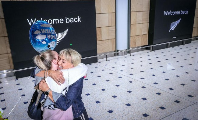 A passenger hugs a family member upon arrival from New Zealand at Sydney International Airport. Credit: AFP Photo