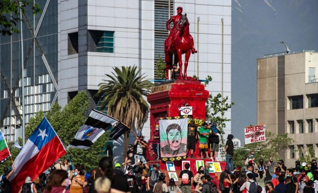 People protest by the General Baquedano monument -painted in red- against Chilean President Sebastian Pinera's government at Plaza Italia square, in Santiago. Credit: AFP Photo
