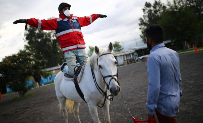 Rafael Aguilar, 32, a health worker and patient, rides on a horse named