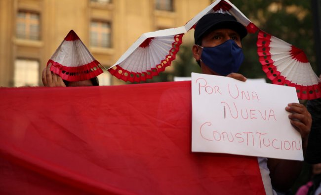 A member of Peruvian community living in Chile holds a sign reading \'for a new constitution\' during a rally to support their compatriots in Santiago, Chile. Credit: Reuters Photo