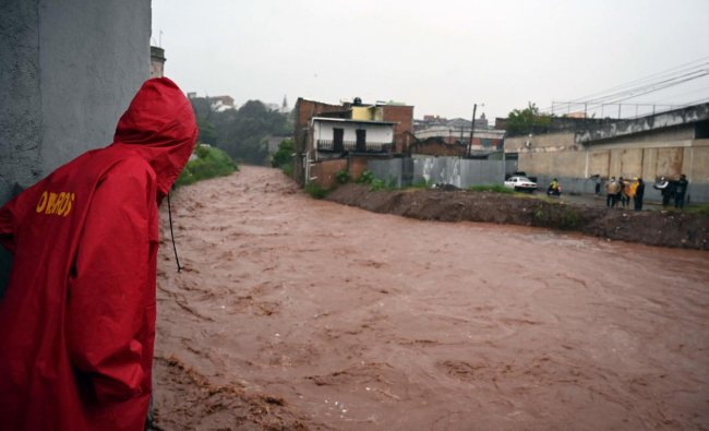 Locals look at the rising level of the Chiquito river, in La Hoya neighbourhood, in Tegucigalpa, following the passage of HurricaneIota. HurricaneIotabarrelled through Central America, after making landfall earlier this week as the strongest Atlantic storm this year along a stretch of Nicaraguan coast devastated by a powerful storm just two weeks ago. Credit: AFP Photo