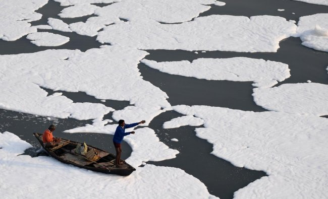 Men row a boat in the polluted waters of river Yamuna covered with foam in New Delhi. Credit: PTI Photo