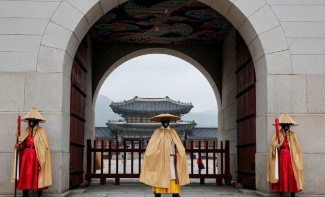 Workers wearing traditional attire wear masks to prevent the spread of the coronavirusduring the daily re-enactment of the changing of the Royal Guards at Gyeongbok Palace in central Seoul, South Korea.Credit: Reuters Photo