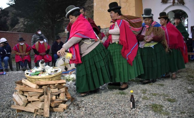 Indigenous women take part in an ancestral ritual to ask Achachilas (mountains) and Pachamama (mother earth) for rain in agriculture lands in Hampaturi, 30 Km northeast of La Paz, Bolivia, where the dam that supplies the capital of water is located. Credit AFP Photo