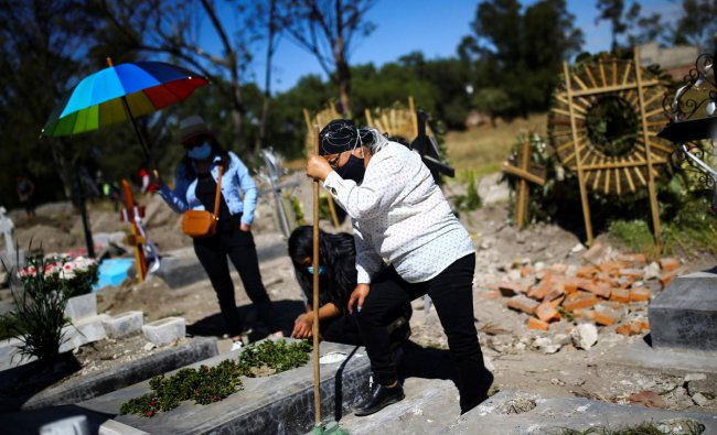 Maru, daughter of Natalia, who died on August of the coronavirusat the age of 86, mourns in front of her grave, as Mexico surpasses 100,000 deaths from the virus, in Mexico City, Mexico. Credit: Reuters Photo