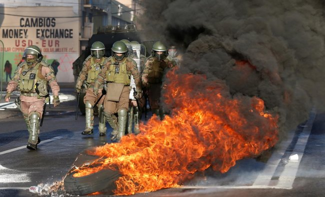 Security forces are seen walking next to tires on fire during a protest against Chile\'s government in Valparaiso, Chile. Credit: Reuters Photo