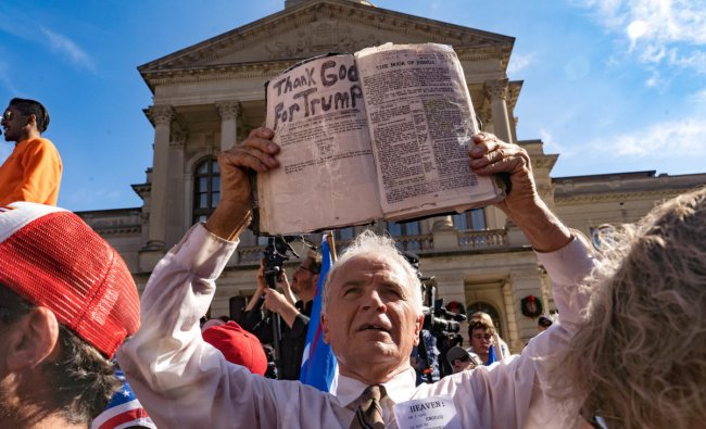 A preacher holds up his Bible while supporters of Donald Trump host a Stop the Steal protest outside of the Georgia State Capital building. Credit: AFP Photo