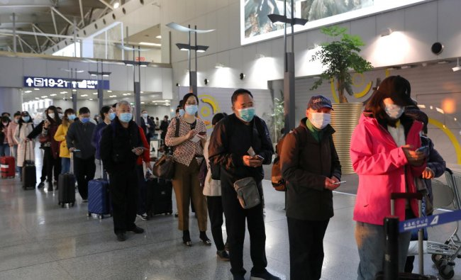 Travellers wearing face masks line up to board a flight at Beijing Capital International Airport, following the global outbreak of the coronavirus disease, in Beijing, China. Credit: Reuters Photo