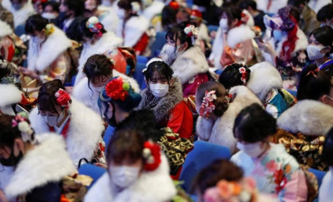 Youths including kimono-clad women wearing protective face masks attend their Coming of Age Day celebration ceremony amid the coronavirus disease outbreak, in Yokohama, Japan. Credit: Reuters.