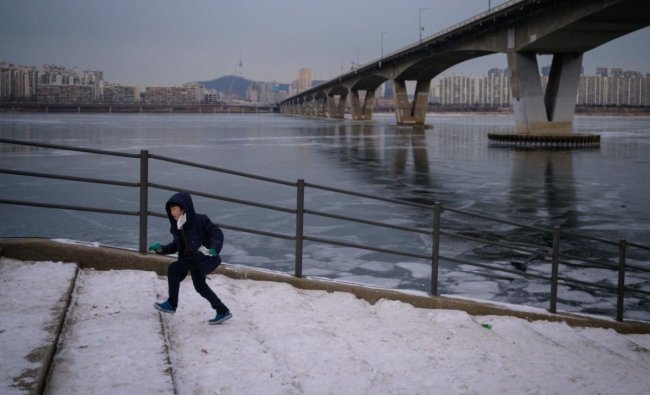 A photo taken on January 10, 2021 shows a child running up steps before a bridge over the frozen Han river and Seoul city skyline. Credit: AFP.