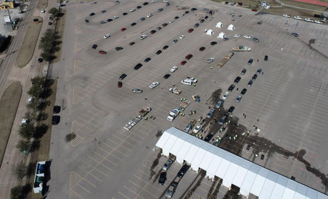 Cars line up to receive free cases of water after the city of Houston implemented a boil water advisory following an unprecedented winter storm, in an aerial photograph taken at Delmar Stadium in Houston, Texas. Credit: Reuters photo.