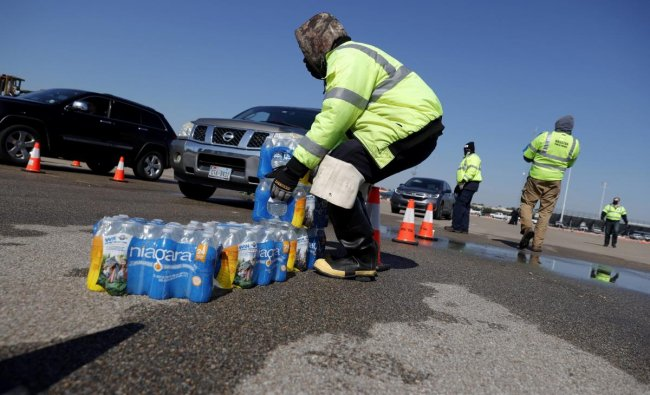 Workers with Houston Public Works prepare to load cases of water into waiting cars during a mass water distribution at Delmar Stadium on February 19, 2021 in Houston, Texas. Credit: AFP photo.