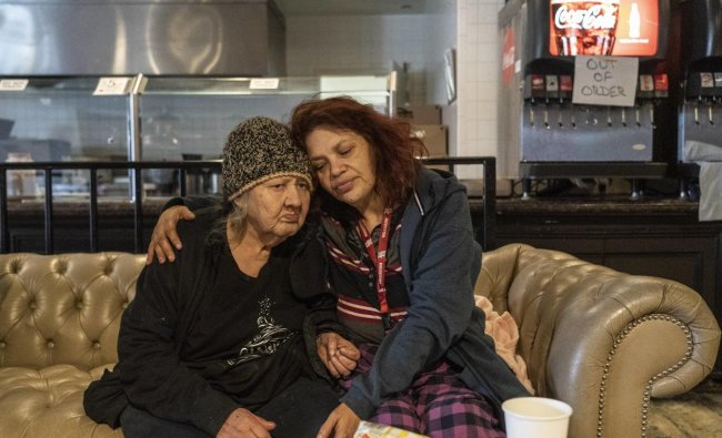 Deloris Sanchez, 56, and Mallissa Lee, 52, sit on a couch while taking shelters at Gallery Furniture store which opened its door and transformed into a warming station after winter weather caused electricity blackouts. Credit: AFP photo.