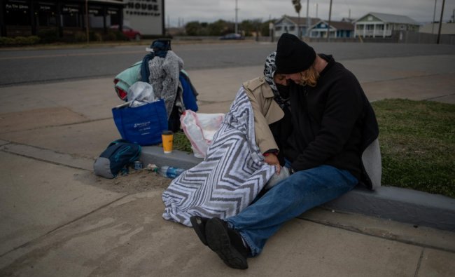Couple Renne Alva, 37, and Travis Wasicek, 43, sit amongst their belongings along Seawall Boulevard as they embrace to keep each other warm. Credit: Reuters photo.