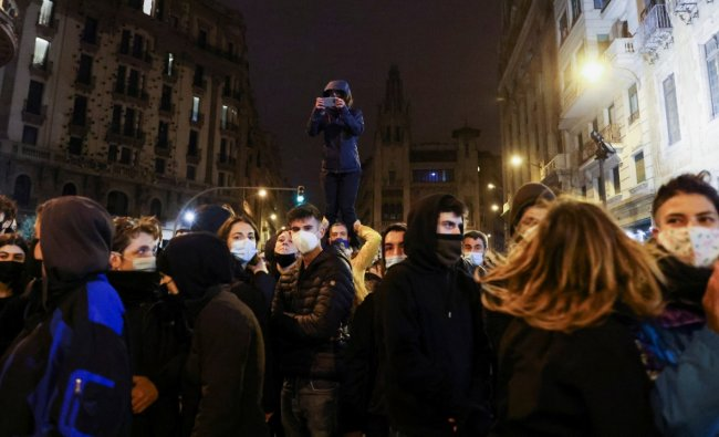 People participate in a protest in support of rap singer Pablo Hasel after he was given a jail sentence on charges of glorifying terrorism and insulting royalty in his songs, in Barcelona, Spain. Credit: Reuters Photo