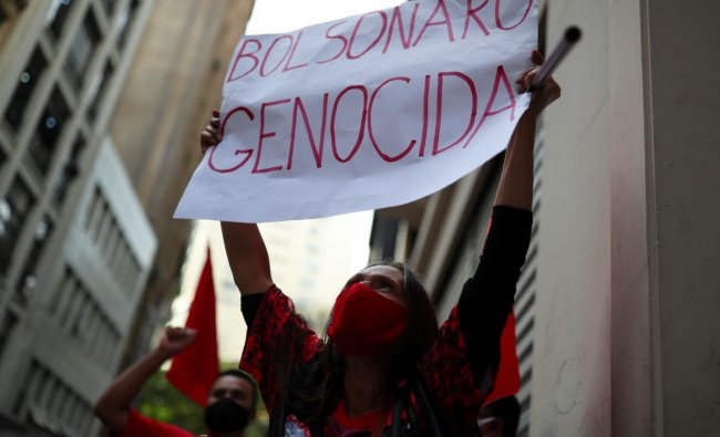A demonstrator from the Roofless Workers Movement (MTST) holds a placard reading \'Bolsonaro genocidal\' during a protest against Brazil\'s President Jair Bolsonaro and his handling of the coronavirus disease crisis, in Sao Paulo, Brazil. Credit: Reuters Photo
