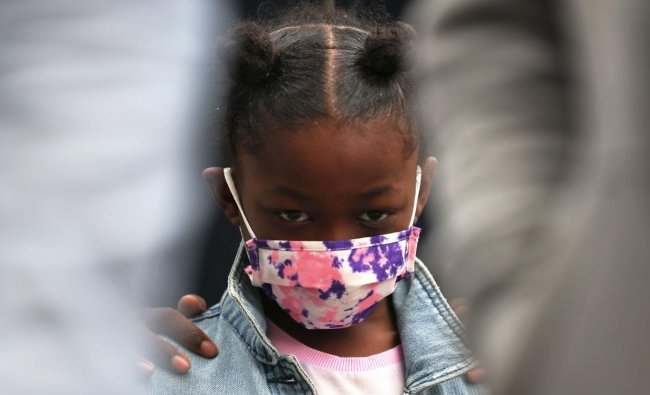 A young child bow\'s her head in prayer at the start of a peace walk to denounce the rise of gun violence in the city in the Harlem neighborhood. Credit: AFP Photo