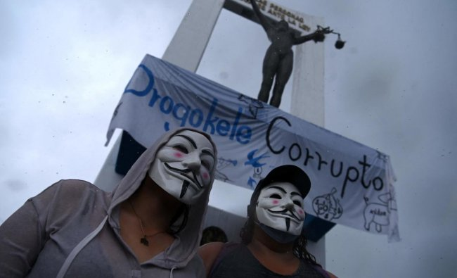 Men wear Guy Fawkes masks during a protest against the latest measures taken by the Legislative Assembly, including the dismissal of the Supreme Court judges and the Attorney General, in San Salvador, on May 2, 2021. Credit: AFP Photo