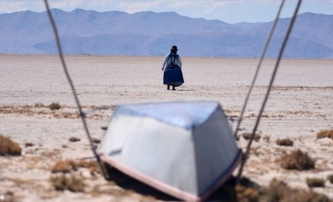 Cristina Mamani walks near an unused boat in Lake Poopo, Bolivia's second largest lake which has dried up due to water diversion for regional irrigation needs and a warmer, drier climate, according to local residents and scientists, in Lake Poopo, Bolivia. Credit: Reuters Photo