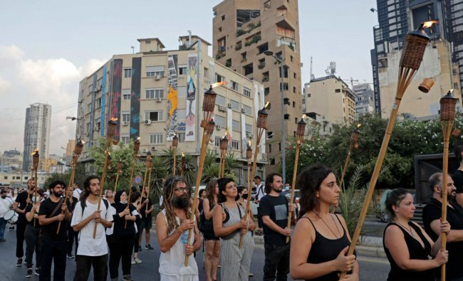 Protesters march with burning torches as they join families of the August 4 victims during a symbolic funeral procession from Beirut port. Credit: AFP Photo