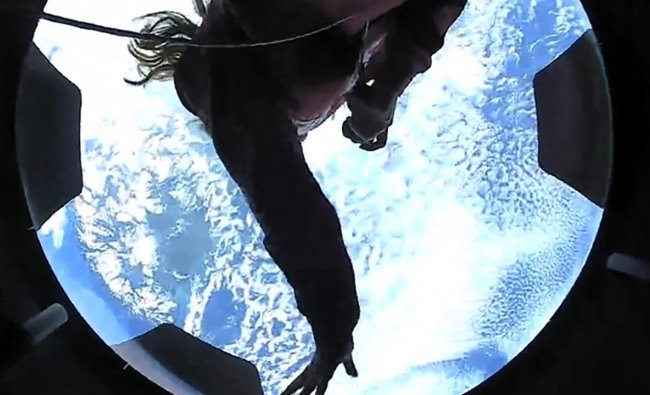 Inspiration4 crew member Hayley Arceneaux looking out of an observation window while in orbit. - SpaceX\'s all-civilian Inspiration4 crew spent their first day in orbit conducting scientific research and talking to children at a pediatric cancer hospital, after blasting off on their pioneering mission from Cape Canaveral the night before. Credit: Inspiration4/AFP