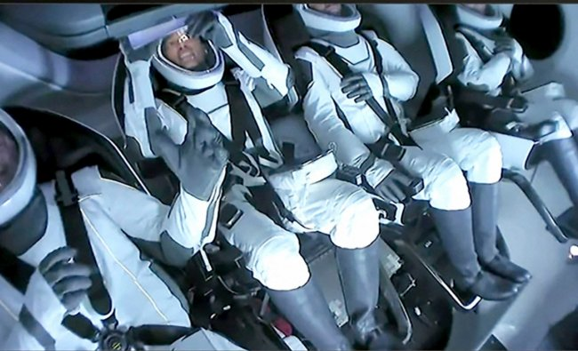 SpaceX video, passengers aboard a SpaceX capsule. Credit: AP Photo
