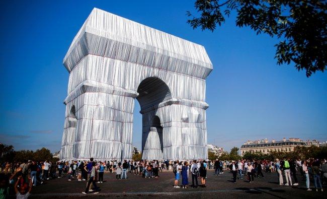 Tourists walk near the Arc de Triomphe in Paris. Credit: AFP Photo