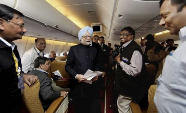 PM Manmohan Singh is also seen working with journalists inside the flight. Credit: Twitter/@KiranKS
