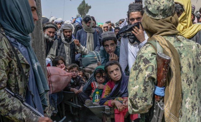 People stand as Taliban members stopped them while rushing to pass to Pakistan from the Afghanistan border in Spin Boldak. Credit: AFP Photo