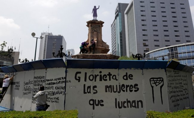 Women paint the fence protecting the site where the statue of Christopher Columbus once stood, after activists unveiled an anti-monument dedicated to \