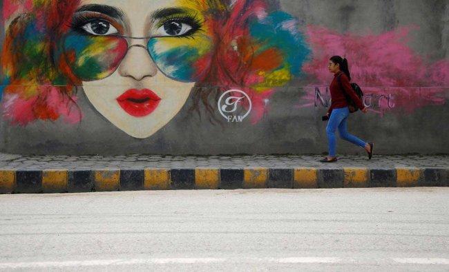 A girl walks past graffiti along the streets of Lalitpur
