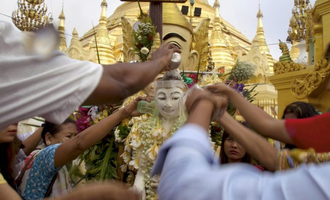 Buddhist devotees pour water to a Buddha statue at Myanmar famous Shwedagon pagoda to mark Myanmar traditional new year Tuesday, April 17, 2018, Yangon, Myanmar. AP/PTI