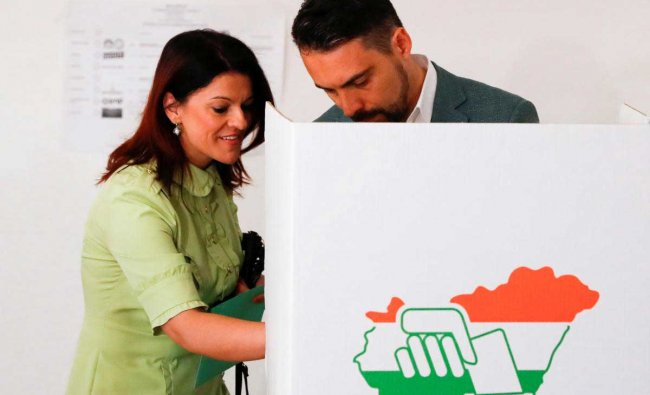 Jobbik party leader Gabor Vona, main opponent to current Prime Minister Viktor Orban and his wife Krisztina Vona-Szabo leave a polling booth to cast their ballots during Hungarian parliamentary elections.