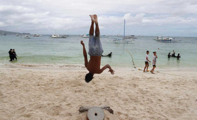 A performer somersaults as he practices for his nightly fire dance along a beach at Boracay.