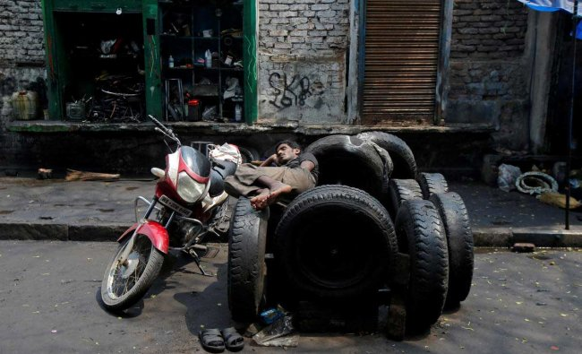 A worker rests on used tyres in front of an automobile repair shop in Kolkata, India. Reuters Photo