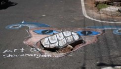 Street artist paints to get potholes fixed