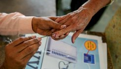 Keeping husband's body at home, woman casts vote