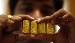 Gold drops 1% on stronger dollar, econ recovery hopes